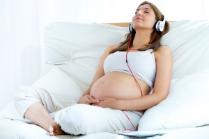 Pregnant woman sitting on sofa at home and listening music in he