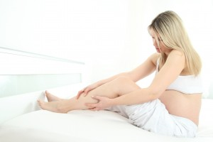 Schwangere Frau haelt ihr Beim mit Wadenkrampf
