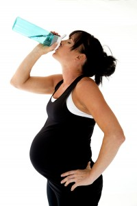 Pregnant model drinking water after her physical fitness workout