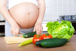 Pregnancy and nutrition - pregnant woman with vegetables